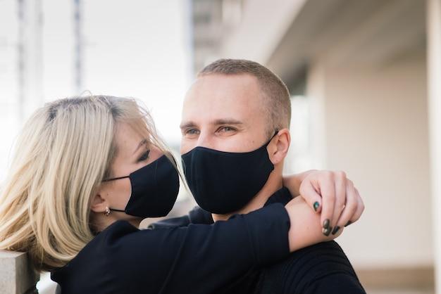Junges paar, das schutzmasken in der stadt trägt