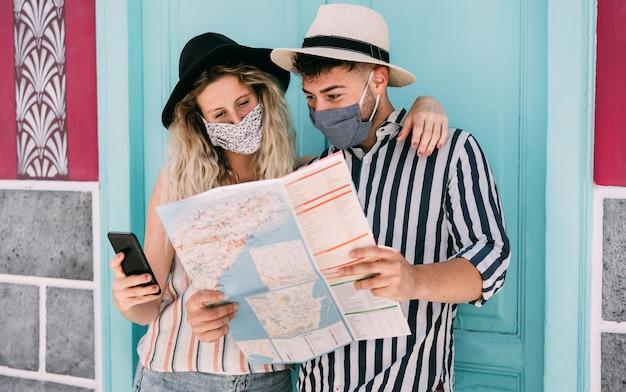 Junges paar, das selfie-foto macht, während gesichtssicherheitsmaske für coronavirus-schutz trägt