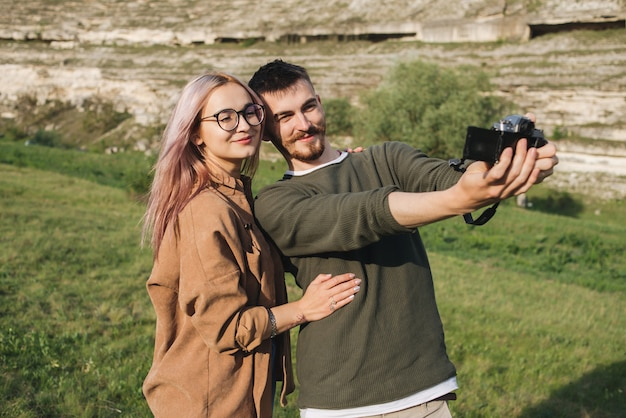 Junges paar, das selfie nimmt glücklicher junger mann und frau, die selbstporträt mit gebirgslandschaft nehmen