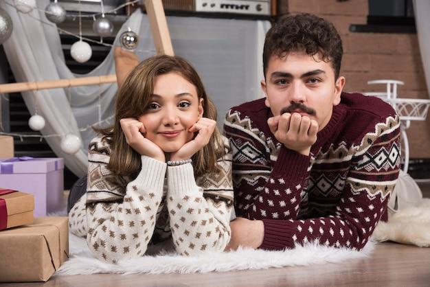 Junges paar, das sich im weihnachtsinnenraum auf dem boden hinlegt.