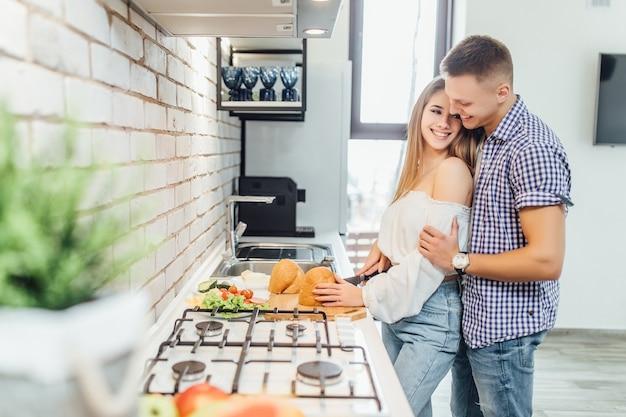 Junges paar, das sich in der küche umarmt, während es abendessen, lifestyle, stilvolle leute macht.