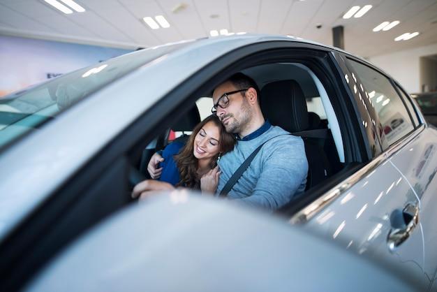Junges paar, das sich in ihrem neuen auto sicher und gesund fühlt