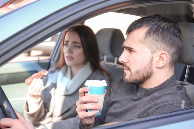 Junges paar, das snack im auto während des staus hat