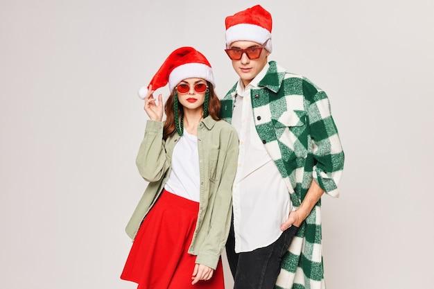 Junges paar, das sonnenbrille-weihnachtsmütze-weihnachtswinterferienmode trägt