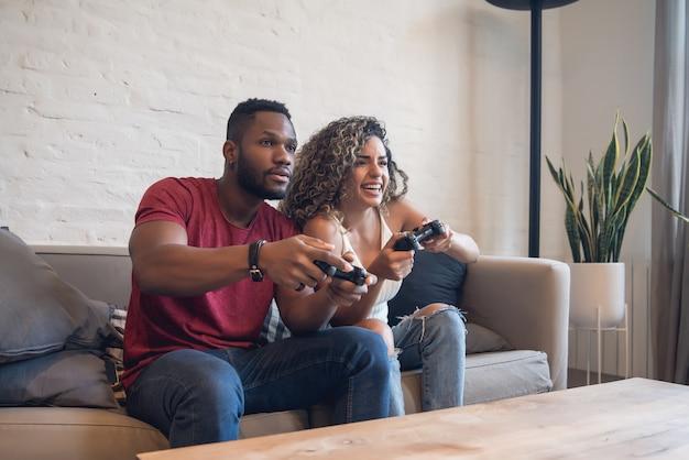 Junges paar, das spaß beim gemeinsamen spielen von videospielen zu hause hat.