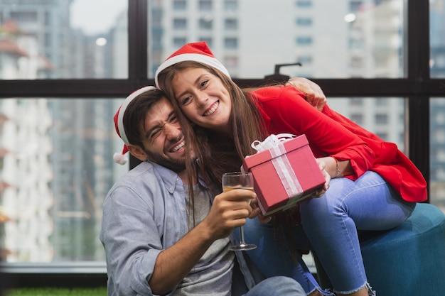 Junges paar, das spaß hat und in die weihnachtsfeier verliebt ist, kaukasischer gutaussehender mann mit champagnerglas und umarmung hübsches mädchen mit geschenkboxen mit weihnachtsmütze feiern neujahrsparty