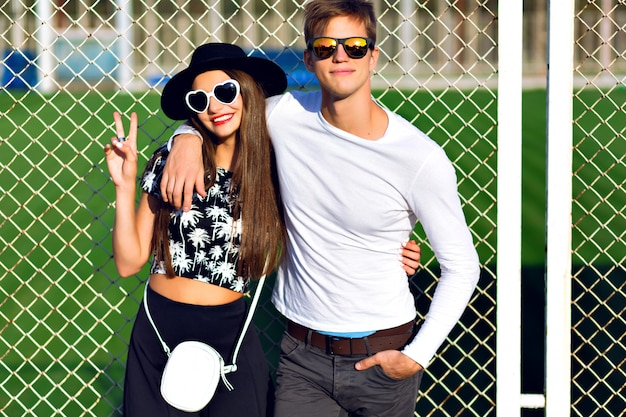 Junges paar, das spaß im sommer, umarmungen, gefühle hat, stilvolle schwarze und weiße kleidung und sonnenbrille tragend