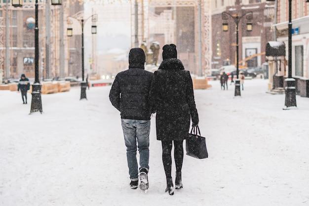 Junges paar, das spaziergang in den stadtstraßen in der wintersaison genießt