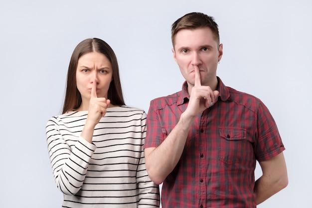 Junges paar, das stille geste zeigt, finger in den mund steckend