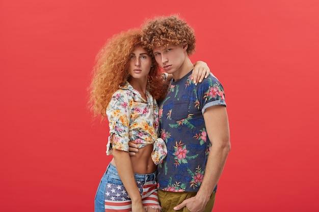 Junges paar, das stilvolle kleidung mit blumenmuster trägt