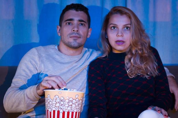 Junges paar, das thrillerfilm im dunklen raum mit popcorn auf sofa volle aufmerksamkeit sieht