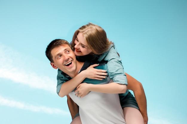 Junges paar, das unter blauem himmel lächelt