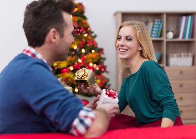 Junges paar, das weihnachtsgeschenk einander austauscht