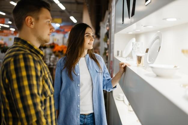 Junges paar, das weingläser im haushaltswarenladen wählt. mann und frau kaufen haushaltswaren im markt, familie im küchengeschirrversorgungsgeschäft