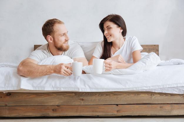 Junges paar, das zu hause beim liegen im bett mit einer tasse aromatischem kaffee entspannt