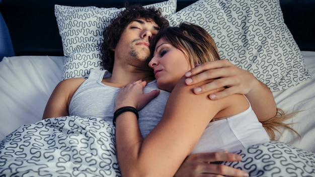 Junges paar, das zu hause im bett umarmt schläft