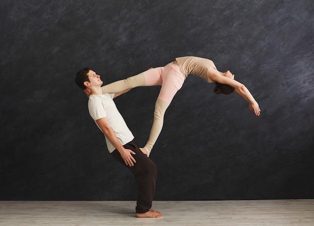 Junges paar, das zusammen acroyoga auf der matte im fitnessstudio praktiziert. frau, die auf mannbeinen balanciert, yoga-vertrauensübung macht. partneryoga, flexibilität, vertrauenskonzept, kopierraum