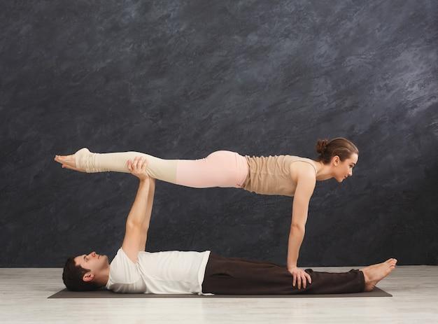Junges paar, das zusammen acroyoga auf der matte im fitnessstudio praktiziert. frau, die plankenhaltung tut, kopienraum, seitenansicht. partneryoga, flexibilität, vertrauenskonzept