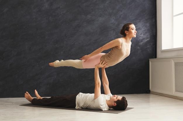 Junges paar, das zusammen acroyoga auf der matte im fitnessstudio praktiziert. frauenfliegen, kopienraum. partneryoga, flexibilität, vertrauenskonzept