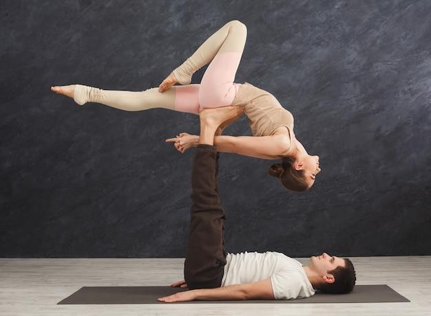 Junges paar, das zusammen acroyoga auf der matte im fitnessstudio praktiziert. frauenfliegen, kopienraum, seitenansicht. partneryoga, flexibilität, vertrauenskonzept