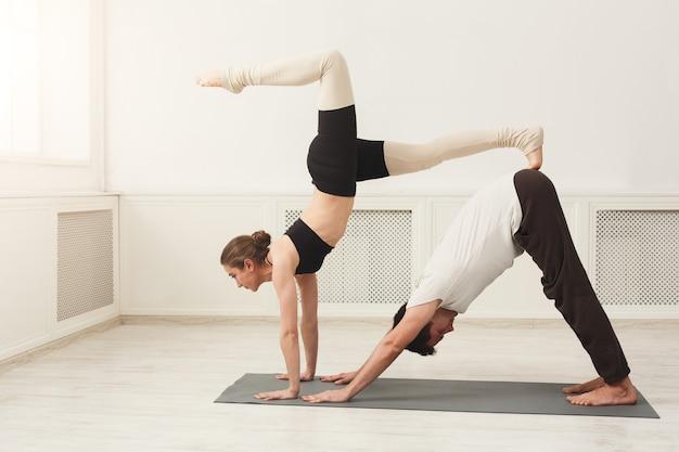 Junges paar, das zusammen acroyoga auf der matte im fitnessstudio praktiziert. mann und frau, die hundeyogahaltung tun, kopienraum. partneryoga, vertrauen, balancekonzept