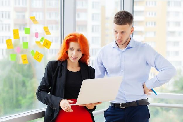 Junges paar, das zusammen an einem laptop im büro arbeitet.