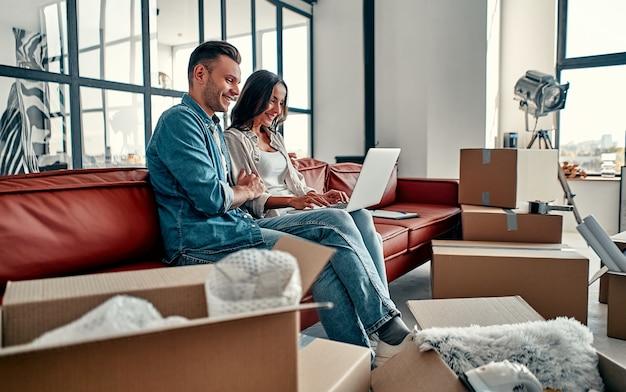 Junges paar, das zusammen auf dem boden sitzt und das drahtlose internet des computers nutzt, während es in ein neues zuhause umzieht. umzug, hauskauf, wohnungskonzept.