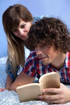 Junges paar, das zusammen ein buch liest, das auf dem bett liegt