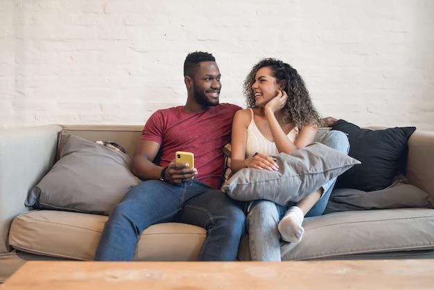 Junges paar, das zusammen ein mobiltelefon benutzt, während es zu hause auf einer couch sitzt.