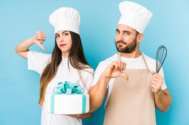 Junges paar, das zusammen einen kuchen kocht, der eine abneigungsgeste zeigt, daumen nach unten.