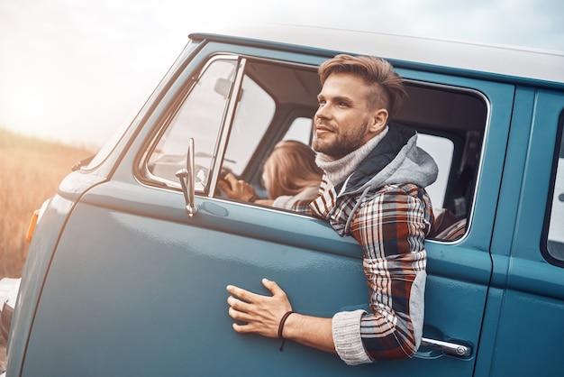 Junges paar, das zusammen einen roadtrip genießt, während es auf den vordersitzen des retro-minivans sitzt?