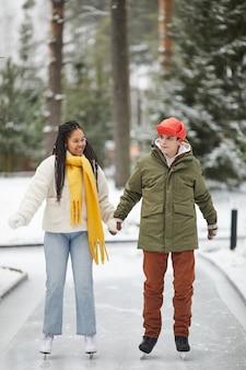 Junges paar, das zusammen händchenhalten und in der eisbahn im freien skatet