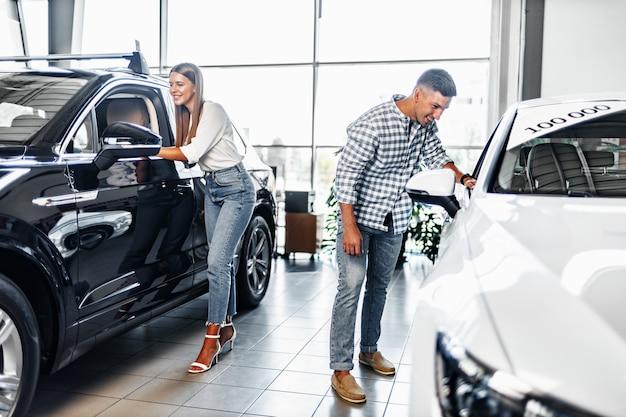 Junges paar, das zusammen ihr neues auto in einem autohaus wählt