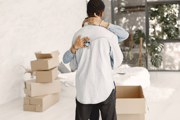 Junges paar, das zusammen in ein neues zuhause einzieht. afroamerikanerpaar mit pappkartons. frau hält schlüssel.