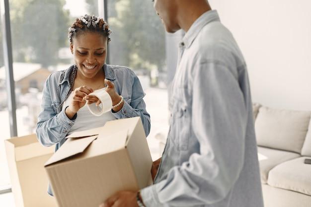 Junges paar, das zusammen in ein neues zuhause einzieht. afroamerikanerpaar mit pappkartons.