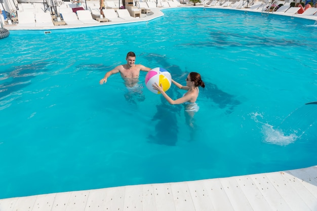 Junges paar, das zusammen in einem resort-swimmingpool spielt und sich einen bunten strandball zuwirft?