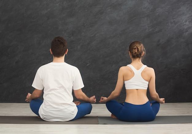 Junges paar, das zusammen meditiert. nicht erkennbarer mann und frau sitzen in der nähe in lotus-pose auf matte, rückansicht, kopierraum