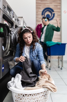Junges paar, das zusammen wäsche im waschsalon macht.
