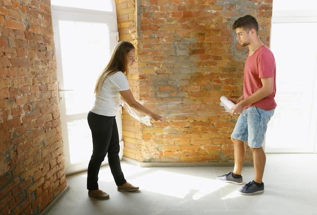 Junges paar, das zusammen wohnungsreparatur macht. verheirateter mann und frau machen renovierung oder renovierung