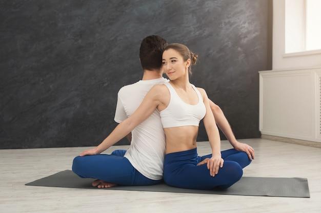 Junges paar, das zusammen yoga praktiziert. mann und frau sitzen rücken an rücken auf matte und drehen sich um den partner, kopieren raum