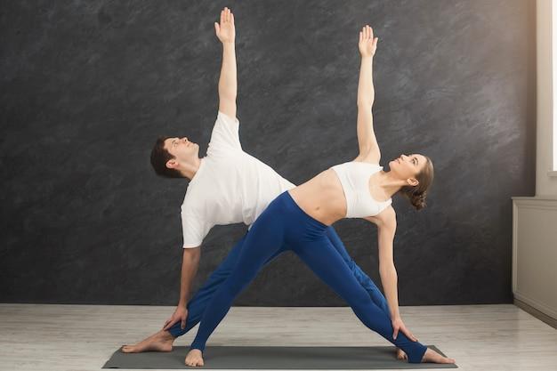 Junges paar, das zusammen yoga praktiziert. mann und frau stehen in der nähe auf der matte, machen gleichgewichtspose und dehnen sich, kopieren raum. partner-yoga-konzept