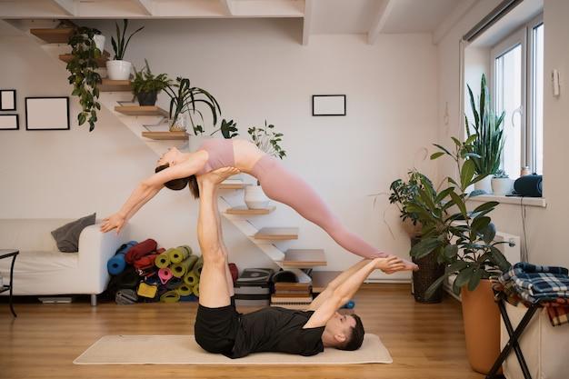 Junges paar, das zusammen zu hause in einem modernen interieur acro yoga praktiziert. hobby, zusammengehörigkeit, gesunder lebensstil