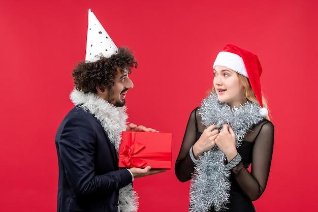 Junges paar der vorderansicht, das feiertagsgeschenke auf der roten wand-emotionsliebesweihnachten austauscht
