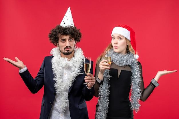 Junges paar der vorderansicht, das gerade neues jahr auf weihnachtsliebe des roten schreibtischfotos feiert