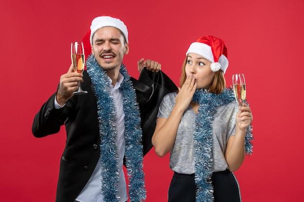 Junges paar der vorderansicht, das neues jahr auf rotem schreibtisch liebt, feiert weihnachtsfeier