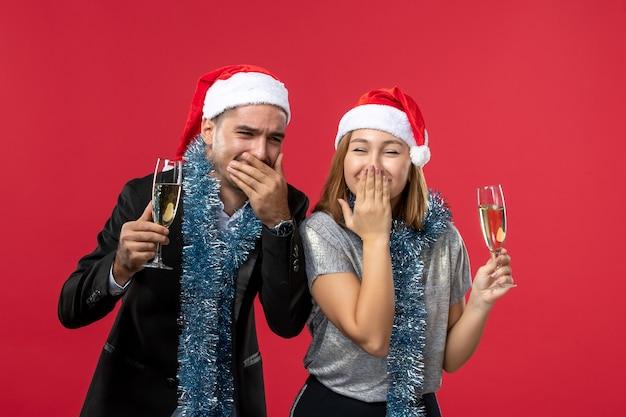 Junges paar der vorderansicht, das neues jahr auf rotem wandliebesweihnachtsfeiergetränk feiert