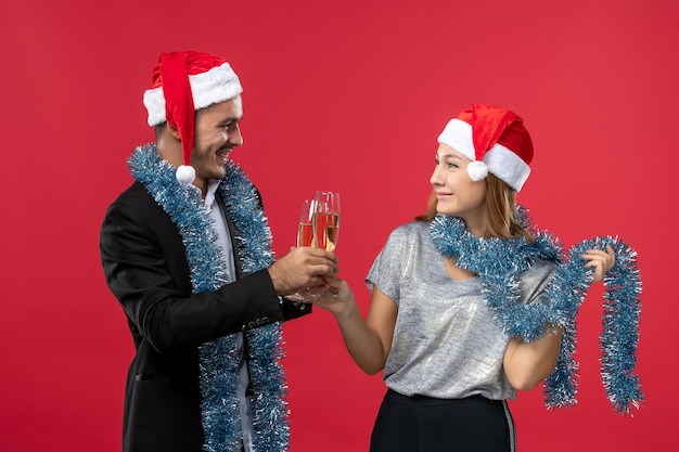 Junges paar der vorderansicht, das neues jahr auf roter wandfarbe feiert, liebt weihnachten