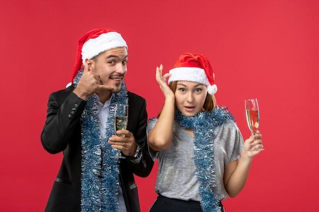 Junges paar der vorderansicht, das neues jahr auf weihnachtsfeier der roten wand feiert, trinkt liebe