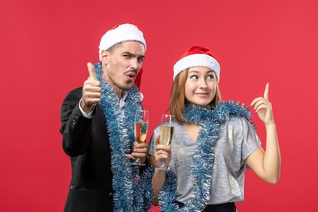 Junges paar der vorderansicht, das neues jahr auf weihnachtsfeier der roten wand feiert