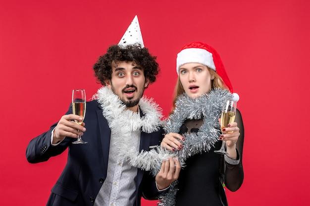 Junges paar der vorderansicht, das neues jahr auf weihnachtsliebe der roten wand feiert